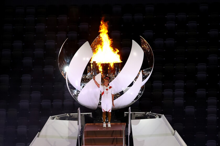 Naomi Osaka of Team Japan holds up the Olympic torch.