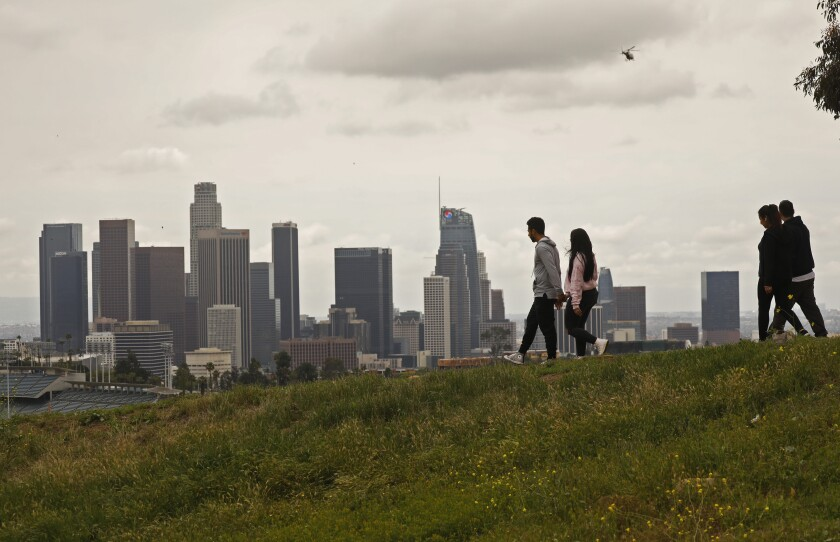 Two couples socially distance themselves while walking through Elysian Park on a cloudy Monday.