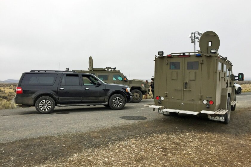 Police and armored vehicles known as Bearcats block the road to the Malheur Wildlife Refuge at an FBI checkpoint outside of Burns, Ore., Friday, Feb. 12, 2016. The FBI allowed a group of reporters to move nearer to the refuge Friday morning as part of a guided tour. The group was not allowed to ent