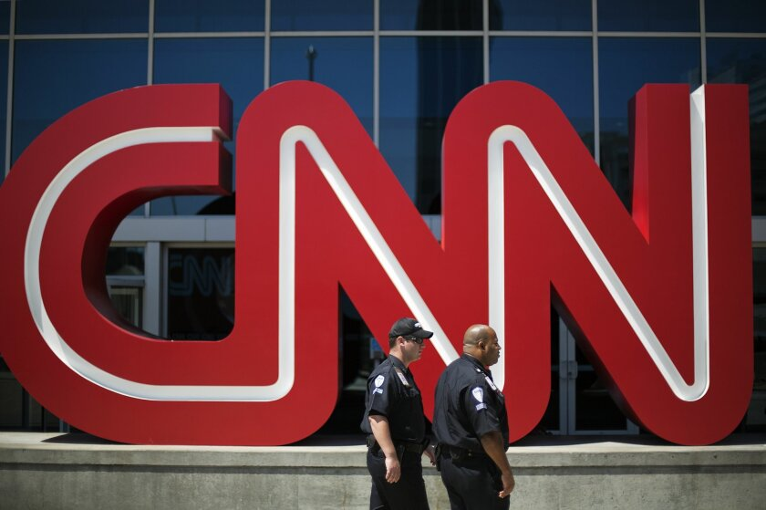 FILE - In this Aug. 26, 2014 file photo, security guards walk past the entrance to CNN headquarters in Atlanta. The international news channel on Tuesday, Nov. 11, 2014 announced it will halt broadcasting in Russia due to recent changes in media legislation. (AP Photo/David Goldman, File)