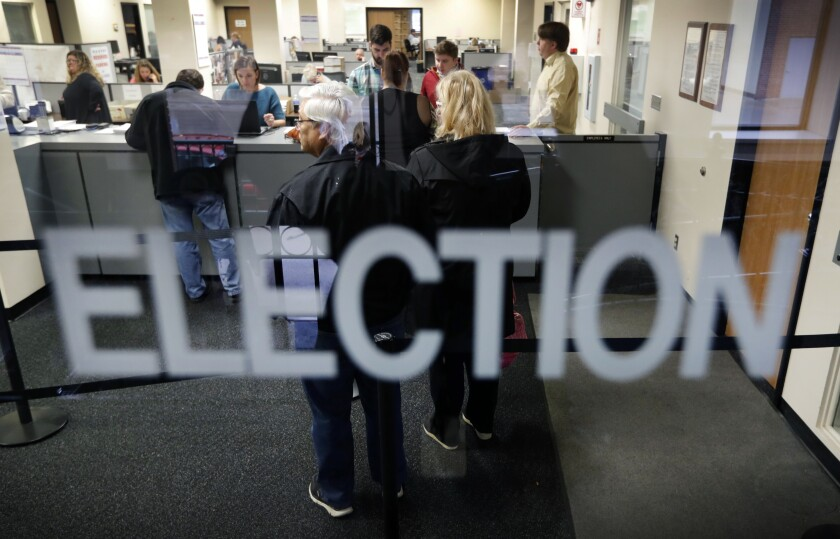 FILE - In this Oct. 8, 2018, file photo, local residents wait in line for their ballot at the Polk County Election office on the first day of early voting for the Iowa general election in Des Moines, Iowa. An Iowa judge has struck down as unconstitutional large portions of a 2017 voting reform law challenged by a Hispanic civil rights group and an Iowa State University student. (AP Photo/Charlie Neibergall)