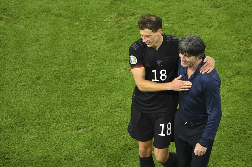 Germany's manager Joachim Loew greets Germany's Leon Goretzka after the Euro 2020 soccer championship group F match between Germany and Hungary at the football arena stadium in Munich, Germany, Wednesday, June 23, 2021. The match ended in a 2-2 draw and Germany progressed to the round of 16. (Matthias Hangst/Pool Photo via AP)