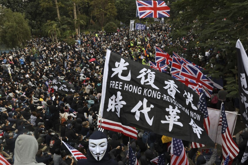 """FILE - In this Sunday, Jan. 19, 2020 file photo, participants wave British and U.S. flags during a rally demanding electoral democracy and call for boycott of the Chinese Communist Party and all businesses seen to support it in Hong Kong. Only five years ago, former British Prime Minister David Cameron was celebrating a """"golden era"""" in U.K.-China relations, bonding with President Xi Jinping over a pint of beer at the pub and signing off trade deals worth billions. Those friendly scenes now seem like a distant memory, with hostile rhetoric ratcheting up this week over Beijing's new national security law on Hong Kong. China has threatened """"consequences"""" after Britain offered refuge to millions in the former colony. (AP Photo/Ng Han Guan, file)"""