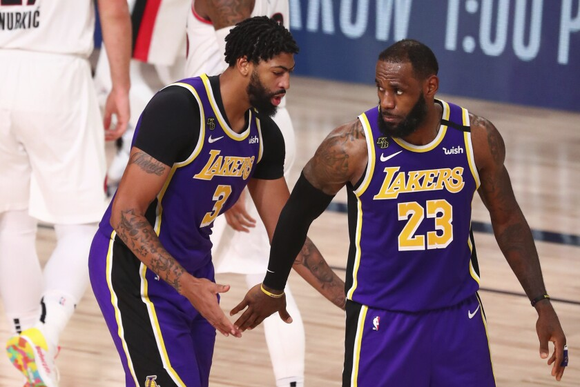 The Lakers' LeBron James, right, reacts after a dunk by teammate Anthony Davis, left, on Aug. 22, 2020.