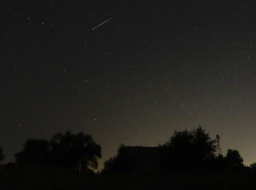 A meteor from the Perseid Meteor Shower is seen over a farm near Tonganoxie, KS.