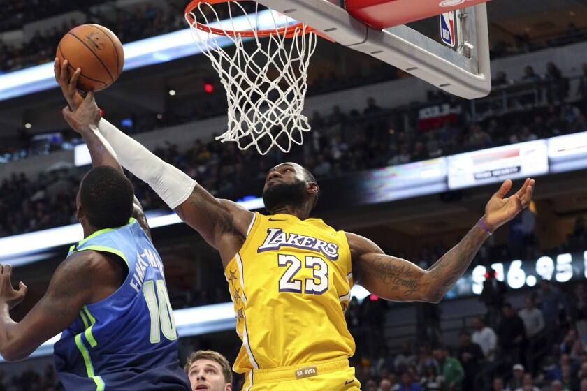 Lakers forward LeBron James attempts a reverse layup against Mavericks forward Dorian Finney-Smith on Jan. 10, 2020, in Dallas.