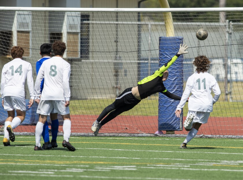 Fountain Valley's Connor Trapp stretches for a ball but comes up short on a goal by Edison's Trent Bellinger.