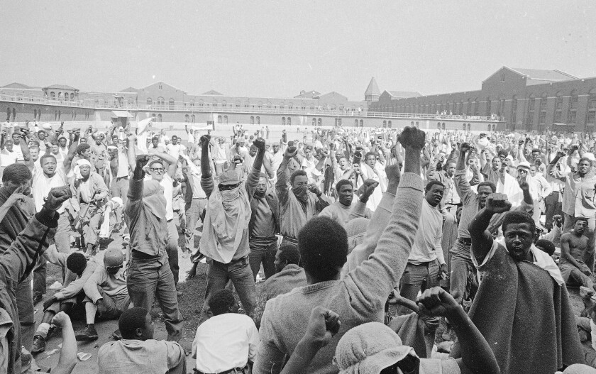 Inmates raise their hands in fists