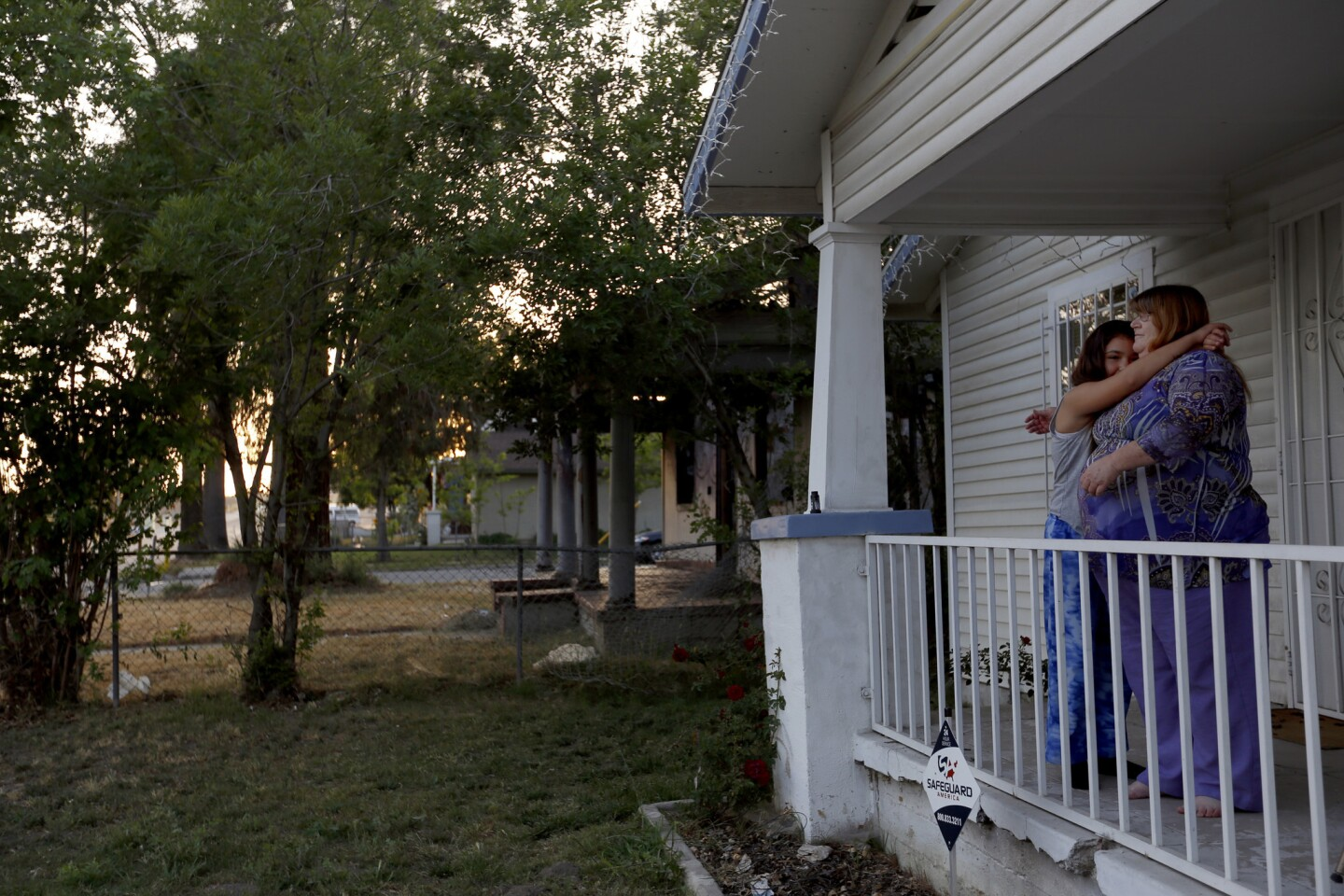 Esmeralda Phillips, 11, left, hugs her grandmother Diane Hayes on Hayes' front porch in San Bernardino. In 2012, a meth fire gutted the home next door and spread to Hayes' home. Hayes rebuilt after the fire, and the burned out abandoned home next door has finally been torn down.