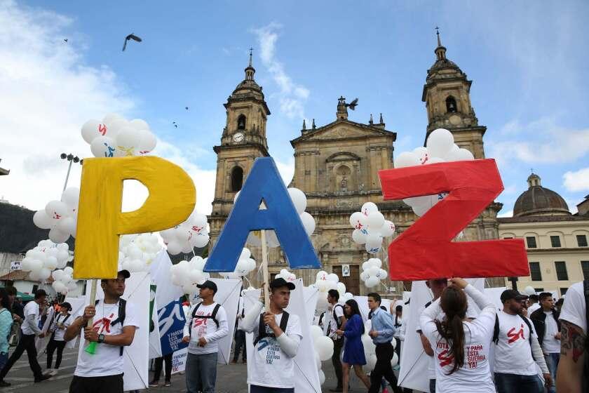 """Personas sostienen letras que forman la palabra """"paz"""" durante una reunión en la plaza Bolívar de Bogotá, el lunes 26 de septiembre de 2016. El gobierno de Colombia y las FARC firmaron un acuerdo de paz para poner fin a más de 50 años de conflicto armado interno. (AP Foto/Jennifer Alarcón)"""