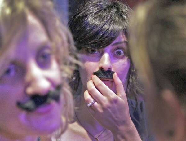 Sara Darouian, center, puts on a mustache along with girlfriends at the Los Angeles Beard & Mustache Competition at the Federal Bar in North Hollywood.