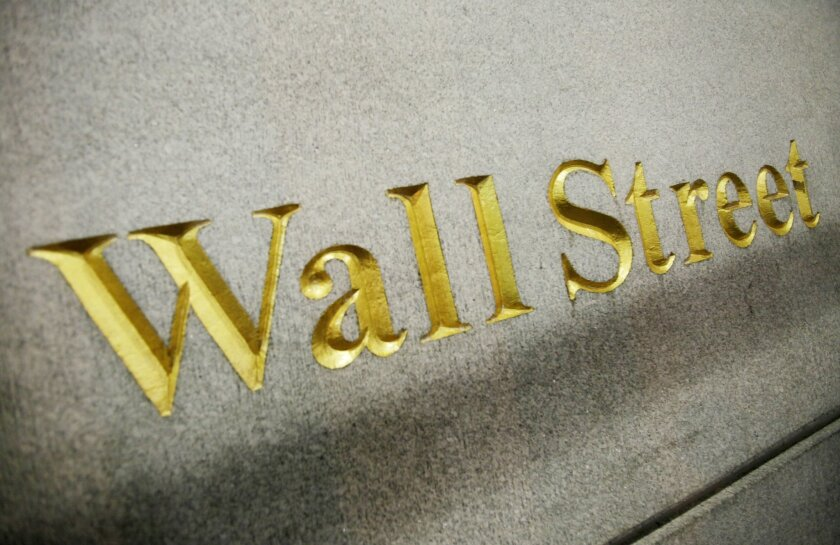 FILE - This Oct. 8. 2014 photo shows a Wall Street address carved into the side of a building in New York.  Global stock markets were subdued Friday, Nov. 6, 2015,  ahead of a U.S. jobs report that's likely to influence whether the Federal Reserve raises interest rates in December. (AP Photo/Mark L