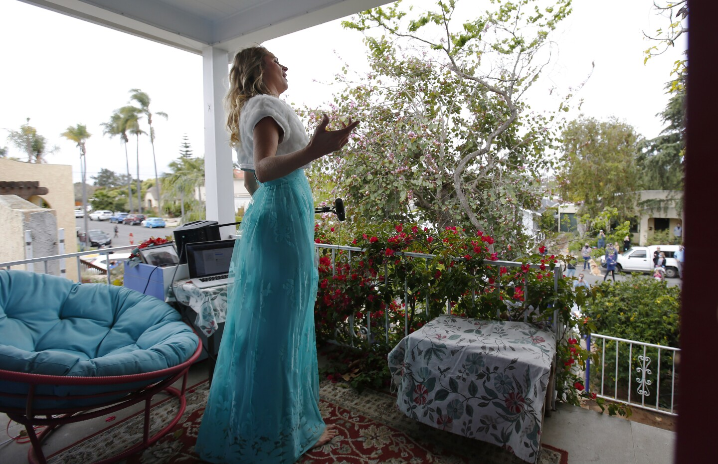 Opera singer Victoria Robertson, a soprano, sings from the porch of her North Park home on April 19, 2020. For the second week in a row, Robertson performed for 15 minutes to a crowd, who kept their distance from each other on the street below.