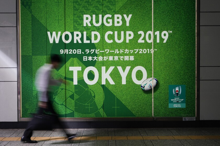 A man walks past a sign promoting the Rugby World Cup Thursday, Oct. 10, 2019, in Tokyo. The powerful typhoon that has caused the first cancellation of the Rugby World Cup games has ended Italy's prospects of reaching the quarterfinals and could upset Scotland's chances of progressing to the knockout stages as well. (AP Photo/Jae C. Hong)