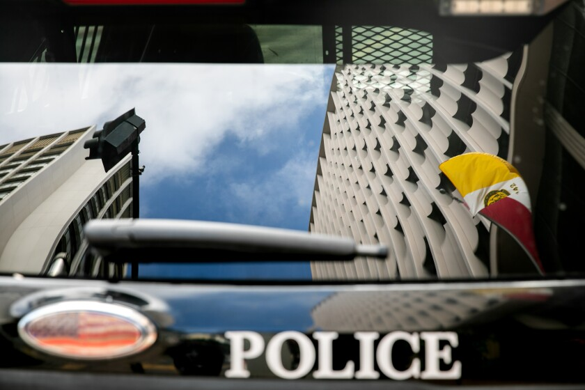 San Diego City Hall is reflected in the rear window of a San Diego Police Department vehicle.