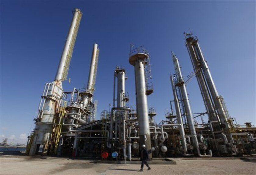 A Libyan oil worker walks in front of a refinery inside the Brega oil complex, in Brega east of Libya, on Saturday Feb. 26, 2011. Production at Brega has dropped by almost 90 percent amid the country's crisis because many employees have fled and few ships are coming to offload the product. (AP Phot