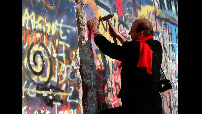 A man chips away at the Berlin Wall near the Brandenburg Gate on the West Berlin side on Nov. 10, 1989.