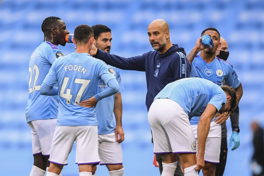 Manchester City's head coach Pep Guardiola, center, talks to his players during the English Premier League soccer match between Manchester City and Bournemouth at the Ethiad Stadium in Manchester, England, Wednesday, July 15, 2020. (Laurence Griffiths/Pool via AP)