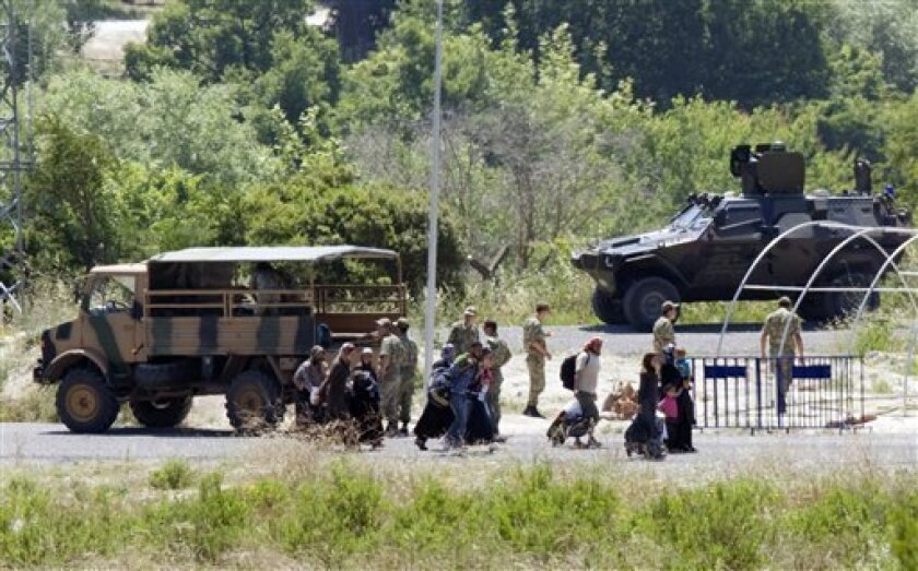 Syrians refugees pass Turkish military vehicles as they cross the border at a crossing point near the Turkish village of Guvecci in Hatay province, Turkey, Thursday, June 23, 2011. Syrian activists claimed that troops backed by tanks and snipers have entered a village along the Turkish border as the regime expands its crackdown on a pro-democracy movement that has posed the gravest challenge to President Bashar Assad's rule.(AP Photo/Burhan Ozbilici)