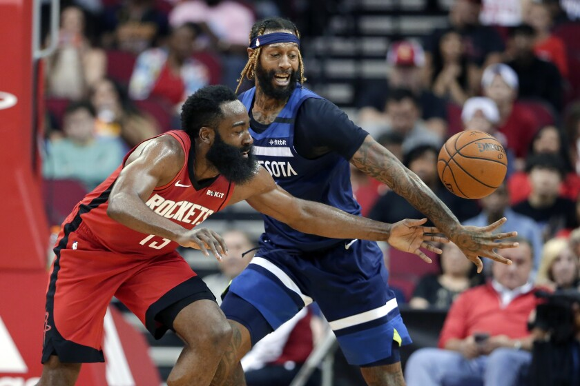 Houston Rockets guard James Harden, left, has the ball knocked away by Minnesota Timberwolves forward James Johnson during the first half of an NBA basketball game Tuesday, March 10, 2020, in Houston. (AP Photo/Michael Wyke)