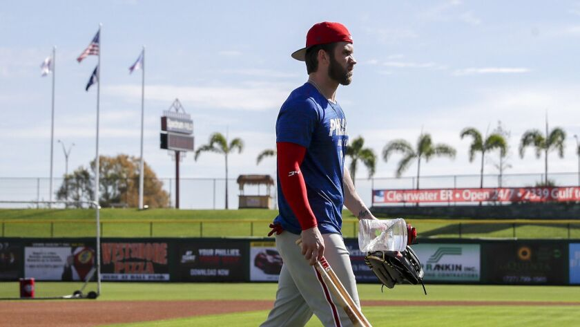 Philadelphia Phillies' Bryce Harper walks to the batting cages during baseball workouts Sunday, Marc