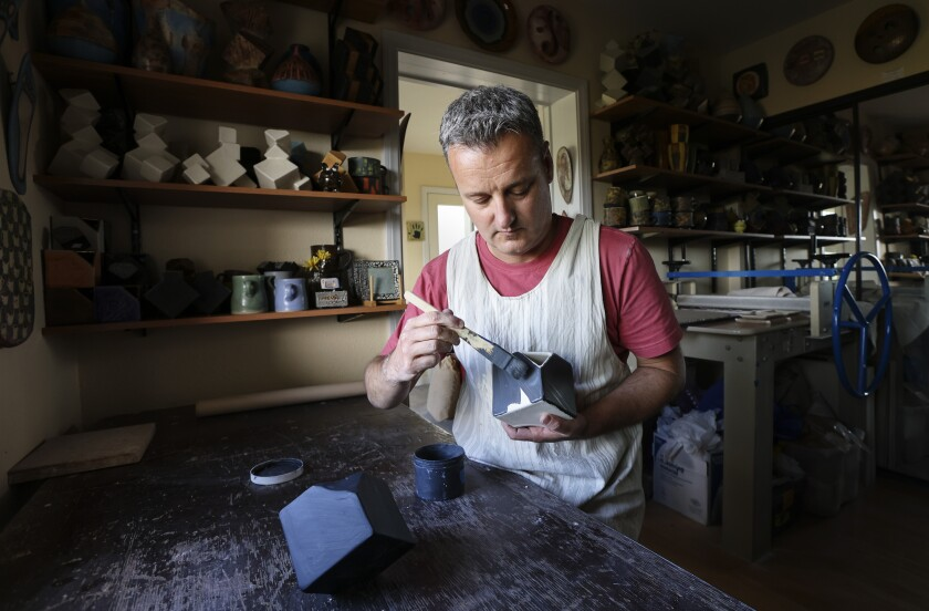 Ceramic artist Pierre Bounaud brushes glaze onto a cube at his home studio in Talmadge.