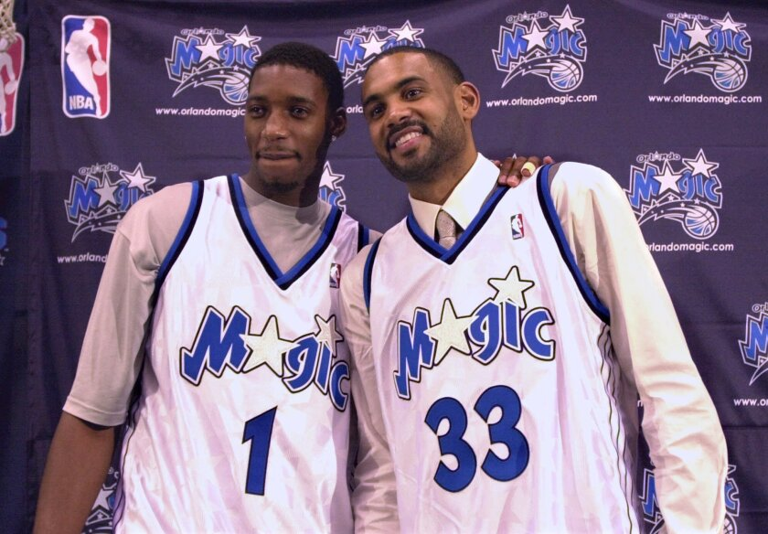 Tracy McGrady, left, and Grant Hill smile after being introduced as the newest members of the Orlando Magic in August 2000.