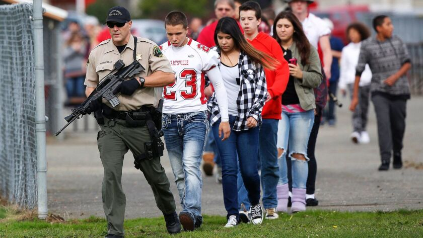 Students are escorted to buses after a 2014 shooting at Marysville Pilchuck High School in Marysville, Wash., that left two dead and four wounded. School shootings were less likely in states with mandatory background checks for gun and ammunition purchases, a new study says.