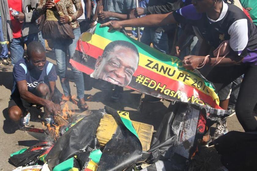 Varios manifestantes queman una pancarta con la cara del presidente de Zimbabue, Emmerson Mnangagwa, en el centro de Harare (Zimbabue) hoy, 1 de agosto del 2018. EFE