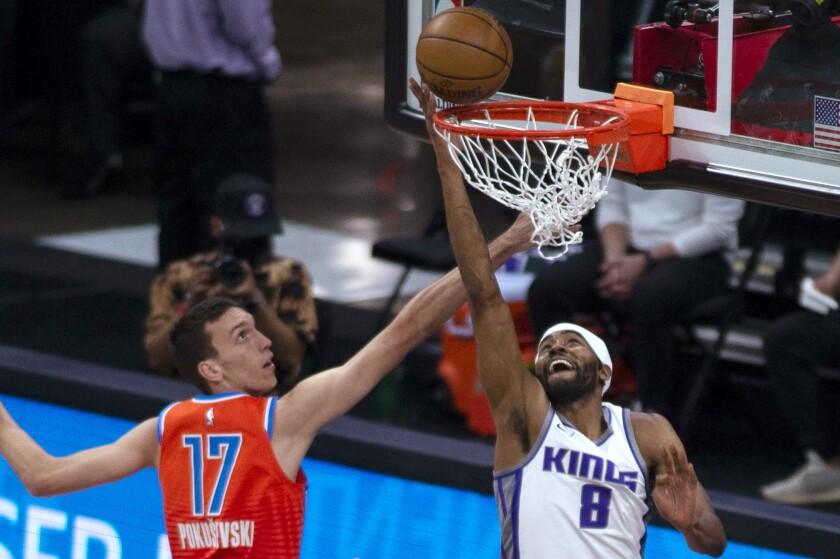 El jugador de los Kings de Sacramento Maurice Harkless (con el 8) encesta mientras el jugador del Thunder de Oklahoma City Aleksej Pokusevski (17) defiende, en el último cuarto de su juego de NBA en Sacramento, California, el domingo 9 de mayo de 2021. (AP Foto/Hector Amezcua)