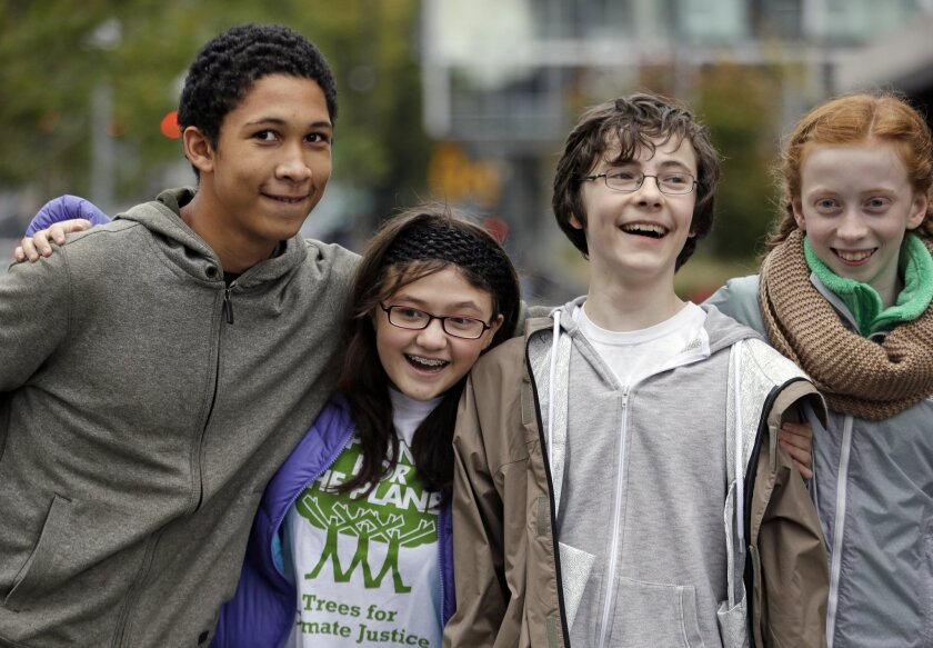 In this photo taken Wednesday, Oct. 28, 2015, teenage environmental activists Aji Piper, left, 15, Lara Fain, 13, Gabriel Mandell, 13, and Wren Wagenbach, 14, playfully pose for a photo after a rally they spoke at in Seattle. The four are among eight youth activists who petitioned Washington state