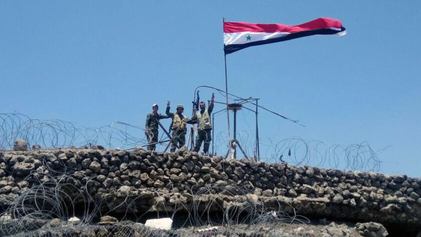 Syrian troops flash the victory sign from a hill in Dara province near the Golan Heights in a photo released July 24, 2018, by the official Syrian Arab News Agency.