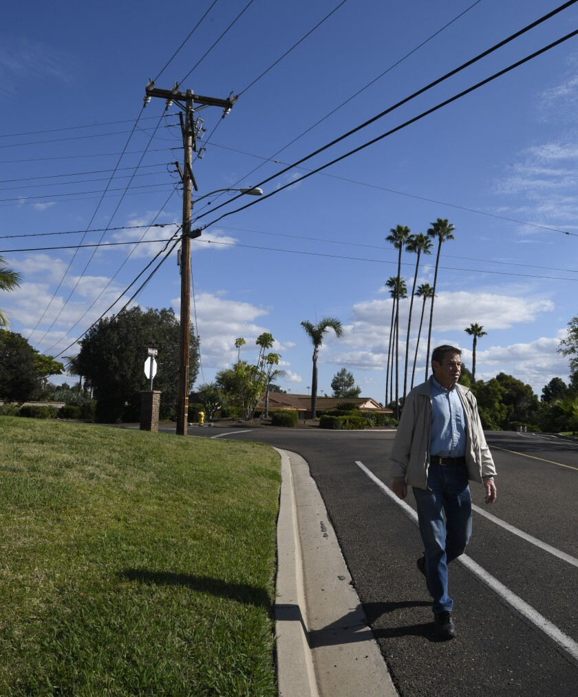 Jose Reynoso, president of the Alvarado Estates Community Assn., walks by a utility pole and power lines on Yerba Santa Drive inside Alvarado Estates in San Diego. City Atty. Mara Elliott says the neighborhood is ineligible to have its utilities undergrounded because it's a gated community.