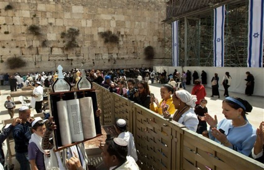 A man holds up a Torah scroll as women stand across a fence at the Western Wall, the holiest site where Jews can pray in Jerusalem's old city, Wednesday, April 10, 2013.  The rabbi of Judaism's holiest prayer site has backed a proposal to establish a prayer section for mixed-gender worship, a groun