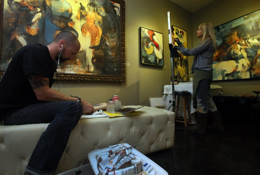 Artists Travis Sevilla, left, and Catherine Edlinger-Kunze both work in acrylics Saturday during an Art-A-Thon at ARtHatch in Escondido. The 24-hour event raises money for youth art programs at the nonprofit gallery on Grand Avenue. Paintings on the walll are by Edlinger-Kunze. Photo by Bill Wechte