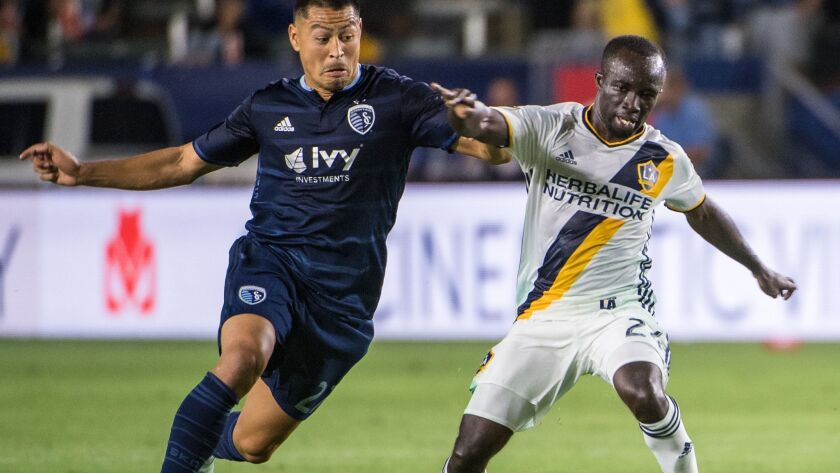 Galaxy's Ema Boateng, right, with the ball as Sporting Kansas City's Roger Espinoza defends during the match in Carson.
