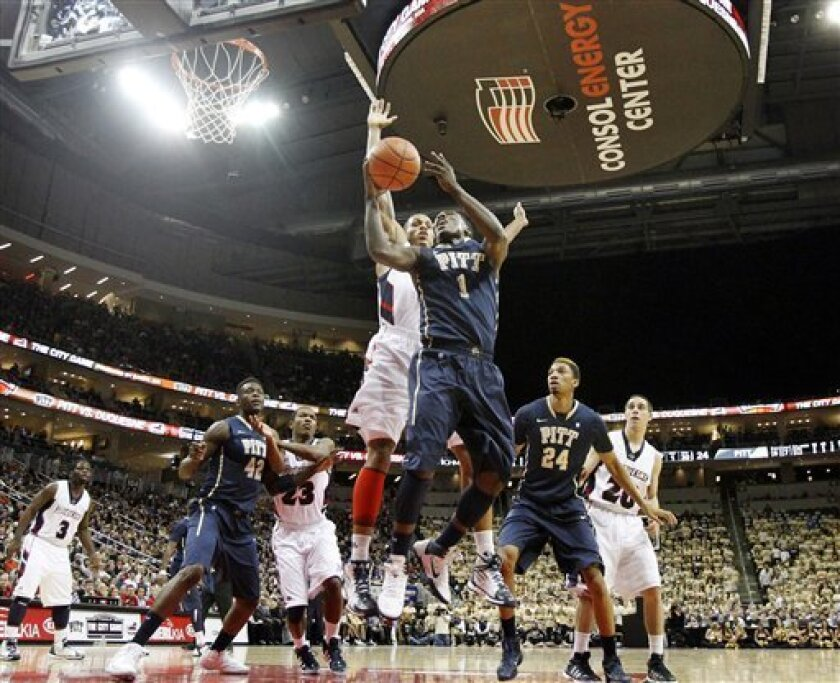 Pittsburgh's Tray Woodall (1) goes past Duquesne's Andre Marhold to score in the first half of an NCAA college basketball game, Wednesday, Nov. 30, 2011, at the Consol Energy Center in Pittsburgh. (AP Photo/Keith Srakocic)