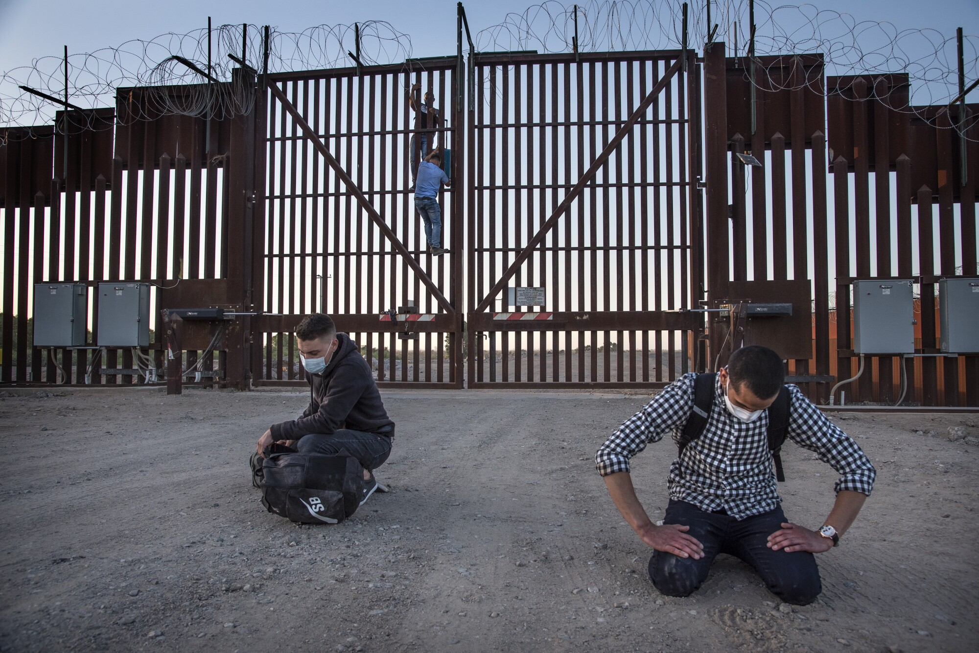 Two Cuban nationals fall to their knees in prayer moments after scaling the U.S./Mexico border fence in San Luis, Arizona