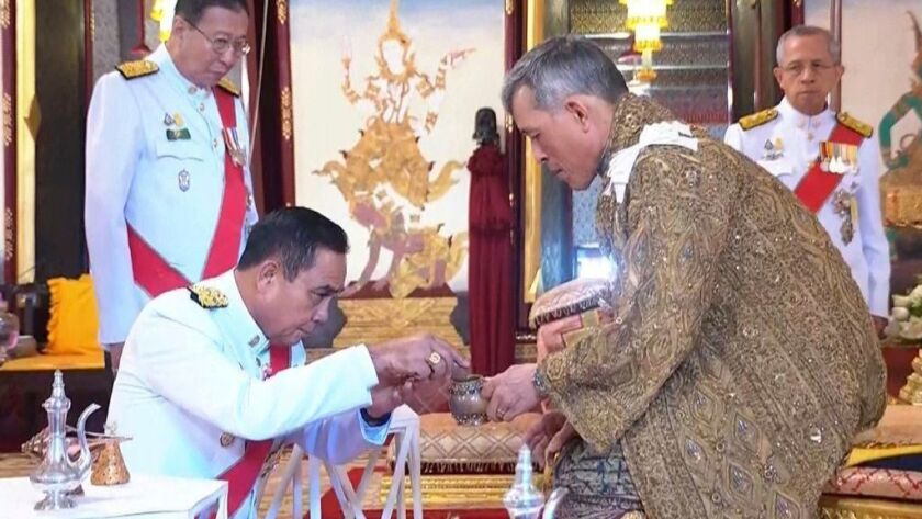 Thai Prime Minister Prayuth Chan-ocha, left, bows as he participates in an anointment ceremony at the coronation of King Maha Vajiralongkorn in Bangkok on May 4, 2019.