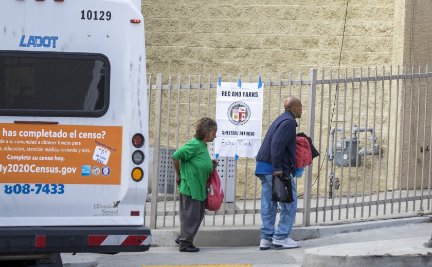 Homeless people from skid row and other areas arrive via bus at the Echo Park Community Center