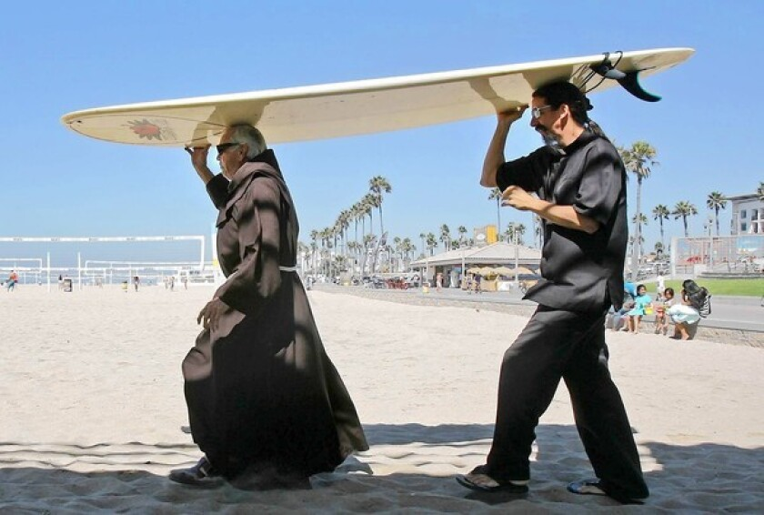 The Rev. Christian Mondor, left, and Father Matt Munoz, carry Mondor's longboard to the water before last year's Blessing of the Waves.