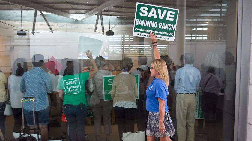 An opponent of the proposed development of the Banning Ranch property carries a sign at the Newport Beach Civic Center as the California Coastal Commission discussed the issue in 2016.