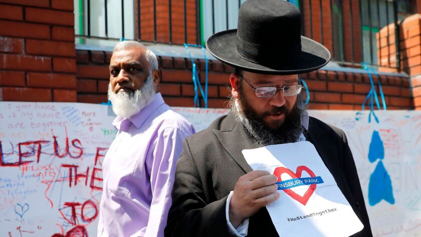 A man holds a sign with a message of solidarity outside Finsbury Park mosque in North London on June