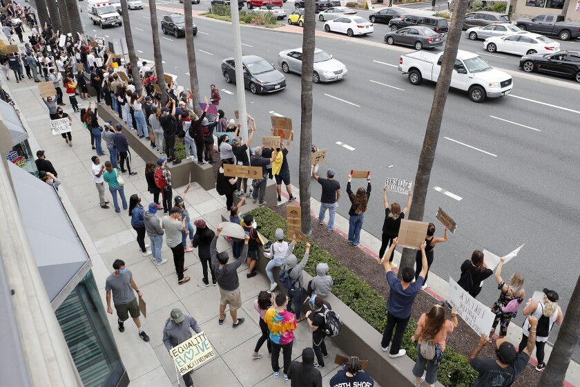 Demonstrators rally during a peaceful protest against police brutality at Triangle Square on Friday in Costa Mesa.