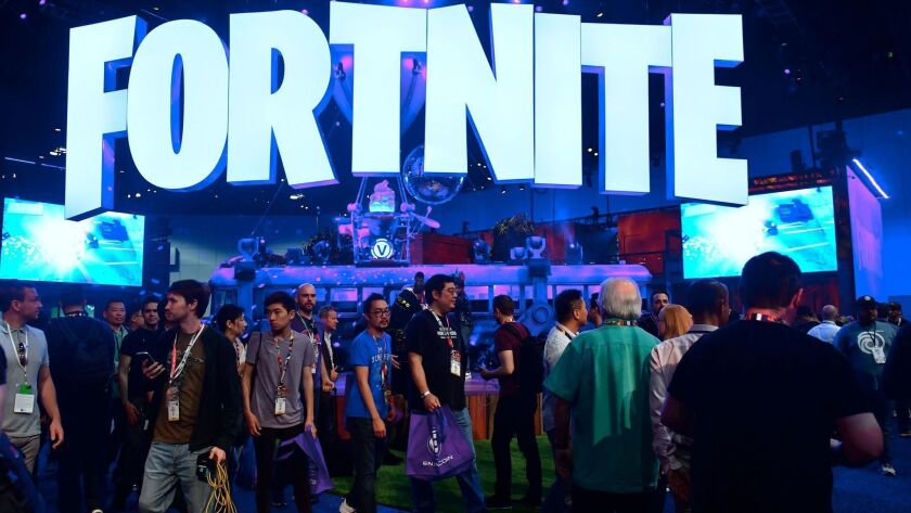 """People crowd the display area for the survival game """"Fortnite"""" at E3 2018 in Los Angeles on June 18."""