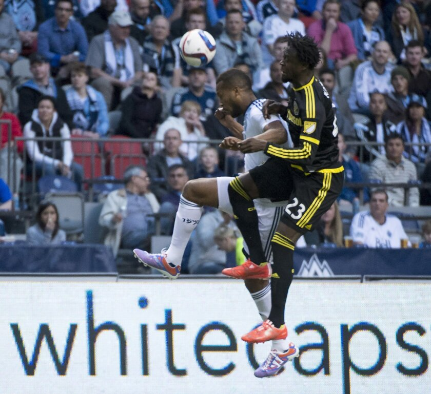 Vancouver Whitecaps FC Kendall Waston, back, fights for control of the ball with Columbus Crew SC Kei Kamara during the first half of MLS soccer action in Vancouver,  British Columbia, Wednesday, April, 8, 2015. (AP Photo/The Canadian Press, Jonathan Hayward)