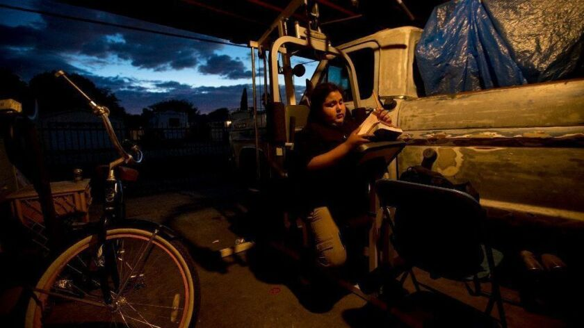 Jesus Rosales, 11, does his math homework sitting on exercise equipment at home in Pacoima on Oct. 1.
