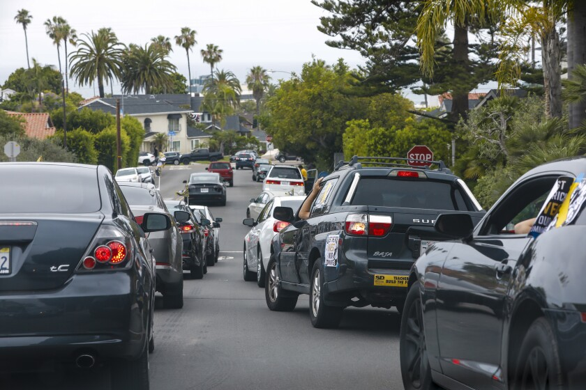 Jose Lopez, with Alliance of Californians for Community Empowerment, led a caravan of cars in  protest in La Jolla.