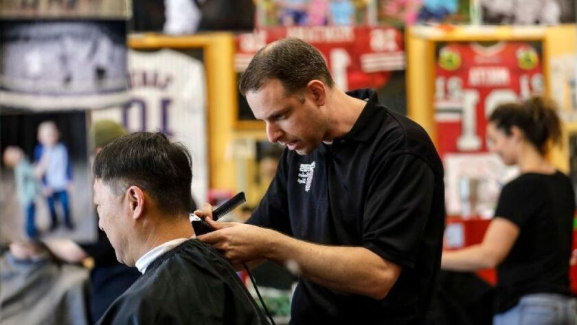 Mark Hylkema, a barber and co-owner of Stew's Barber Shop in Ladera Ranch, had to hire and give employee status to barbers working on contract.