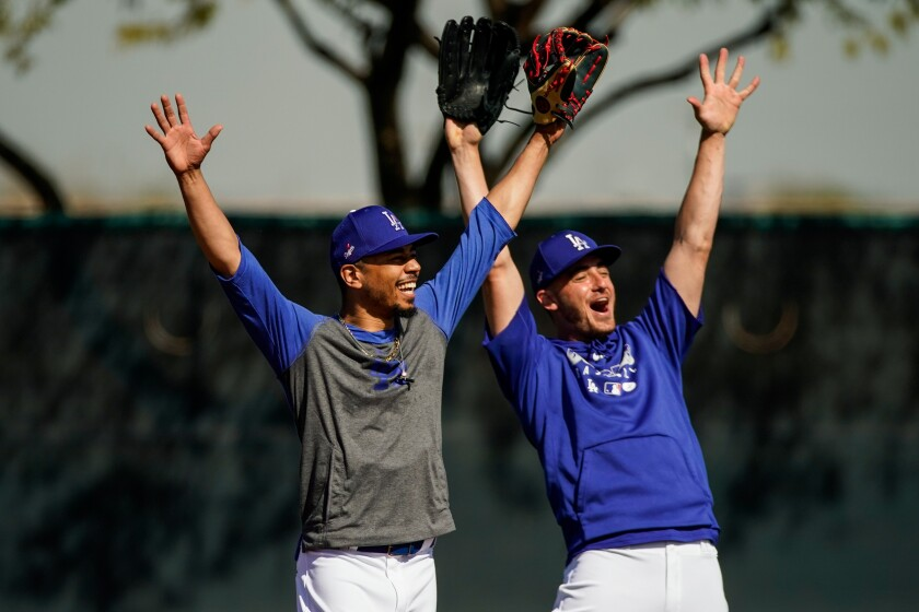 Dodgers teammates Mookie Betts, left, and Cody Bellinger cheer during a spring training practice session at Camelback Ranch on Feb. 19.